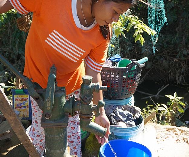Alyssa pumping water into her blue bucket