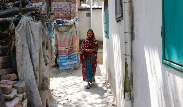 Mitu walks down the alley next to her family home.