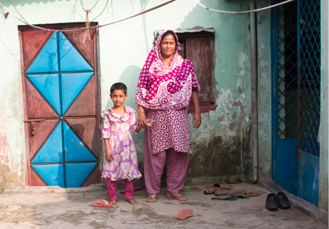 Samta and her daughter in front of their house