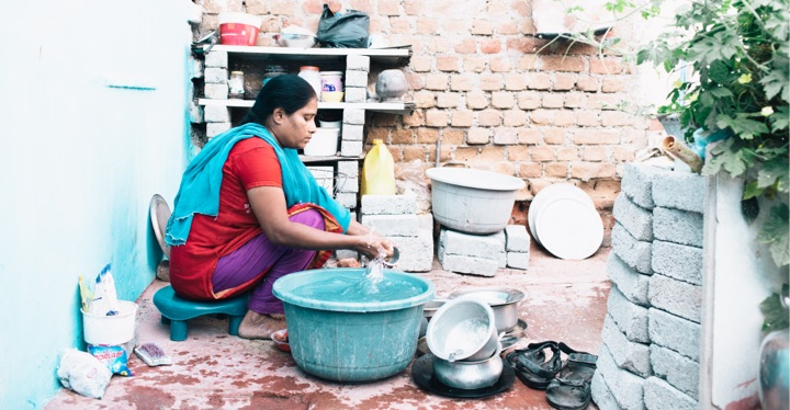 Woman doing laundry in front of her home