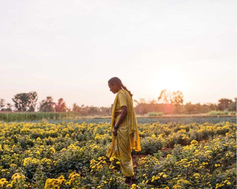 Woman standing in a field of flowers outside of the Mahahalli village